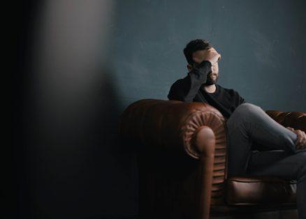 homem sentado preocupado com saúde mental